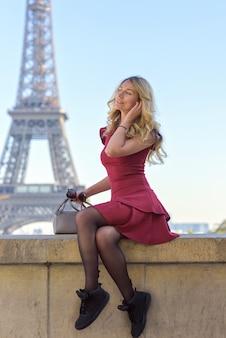 Frau im roten kleid am eiffelturm in frankreich