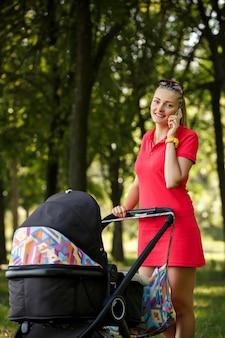 Frau im roten kleid, das auf smartphone spricht und mit kinderwagen im park geht