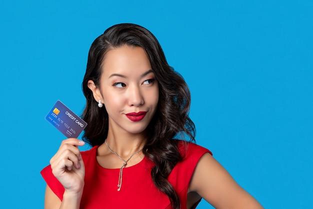 Frau im roten kleid, das in der hand kreditkarte zeigt