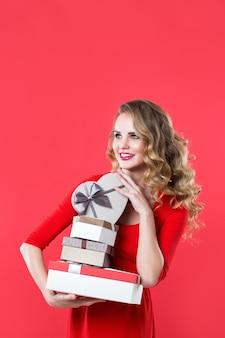 Frau im roten kleid hält viele kisten über rotem hintergrund. ausdrucksstarke mimik.