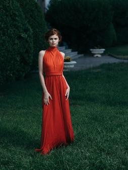 Frau im roten kleid luxusprinzessin maskerade charme grüne blätter.