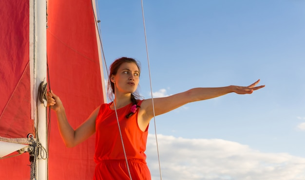 Frau im roten kleid mit ängstlichem gesichtsausdruck, die auf einem segelboot steht, zeigt die hand nach vorne