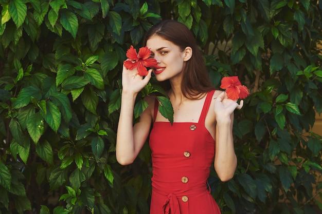 Frau im roten kleid mit blume