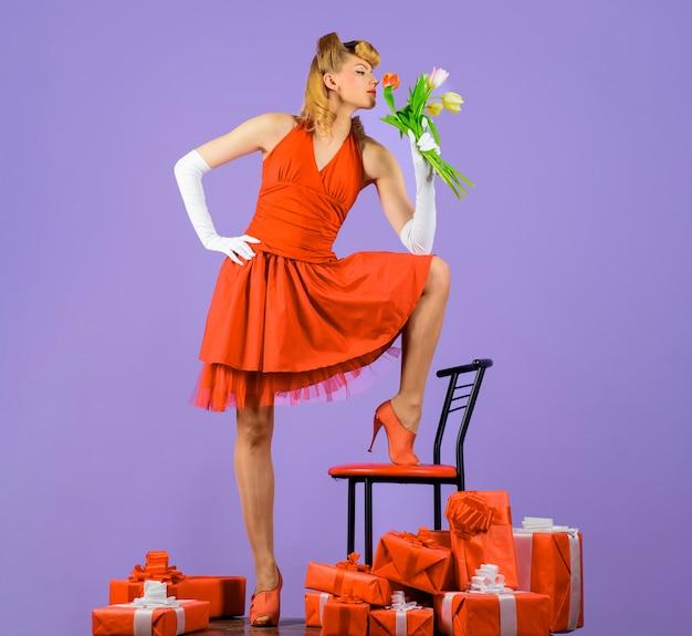 Frau im roten kleid mit retro-frisur glückliche valentinstagblumen und geschenk glückliches mädchen mit geschenk
