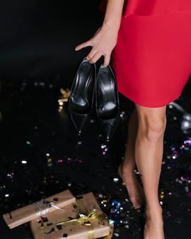 Frau im roten kleid mit schuhen auf party
