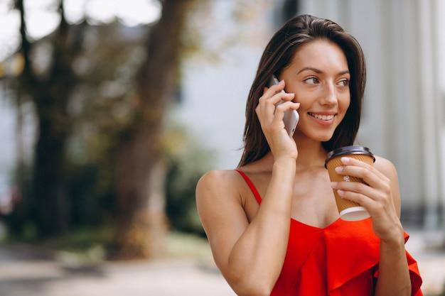 Frau im roten kleid unter verwendung des telefons und des trinkenden kaffees