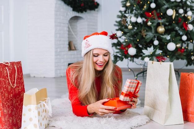 Frau im roten lügen auf boden mit geschenkbox