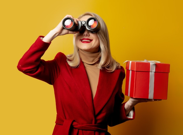 Frau im roten mantel mit fernglas und geschenkbox auf gelber wand