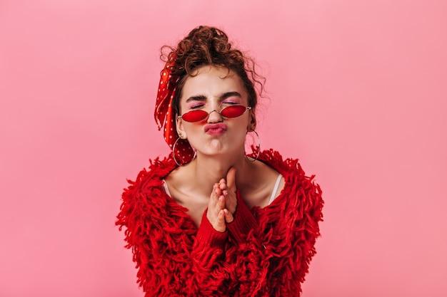 Frau im roten outfit und in den stilvollen brillen, die lustiges gesicht auf rosa hintergrund machen