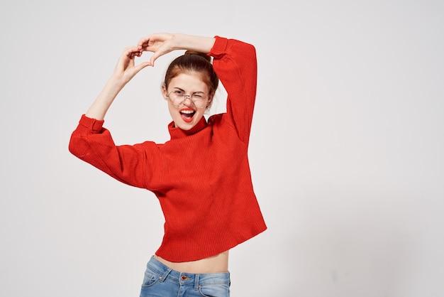 Frau im roten pullover hält hände vor ihrem brillen-spaß-make-up