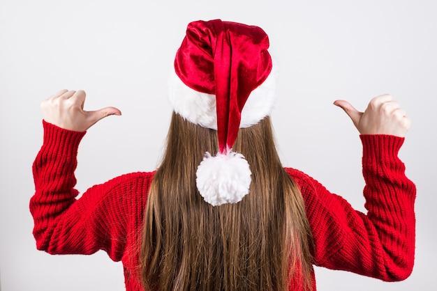 Frau im roten pullover und in der weihnachtsmütze, die finger auf sich zeigt