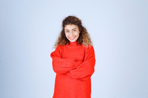 Frau im roten sweatshirt, die fröhliche und positive posen gibt.