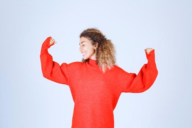 Frau im roten sweatshirt, die ihre faust zeigt und ihre macht bedeutet.