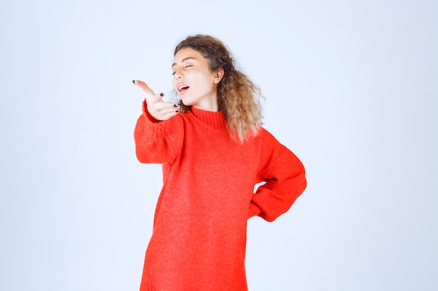 Frau im roten sweatshirt, die jemanden nach vorne zeigt.