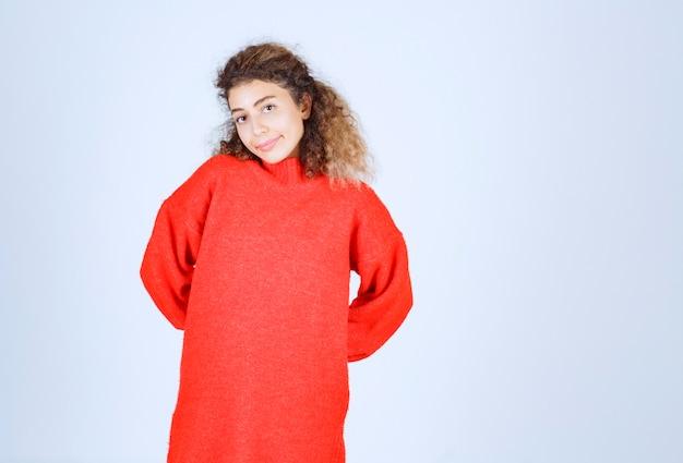 Frau im roten sweatshirt, die neutrale posen gibt.