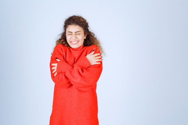 Frau im roten sweatshirt, die sich kalt fühlt.