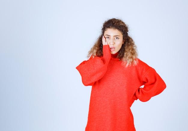 Frau im roten sweatshirt sieht verwirrt und nachdenklich aus.