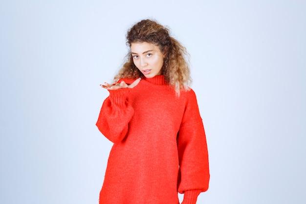 Frau im roten sweatshirt zeigt die maße eines objekts.