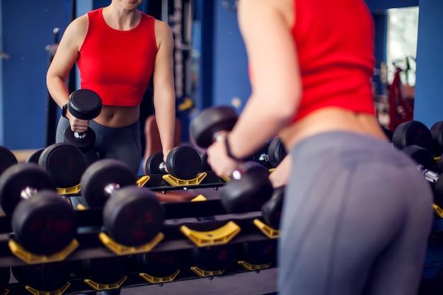 Frau im roten top, die hanteln vor dem spiegel im fitnessstudio nimmt. rückansicht. menschen-, fitness- und lifestyle-konzept