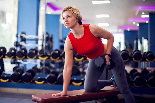 Frau im roten top mit kurzen blonden haaren trainiert rückenmuskulatur im fitnessstudio. menschen-, fitness- und lifestyle-konzept