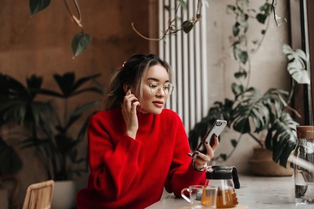 Frau im roten übergroßen outfit und in der brille hält smartphone