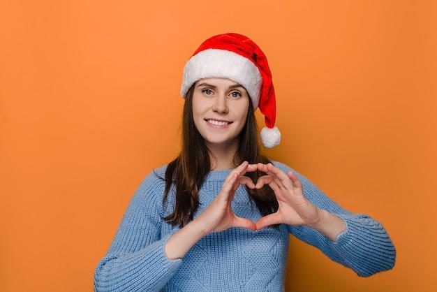 Frau im roten weihnachtshut, macht herzgeste