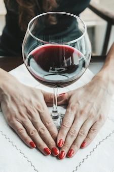 Frau im roten weinglas halten. ein junges schönes mädchen in einem schwarzen kleid sitzt in einem restaurant und trinkt wein aus einem glas. nahaufnahme einer jungen frau, die ihre hand mit glas rotwein hält?