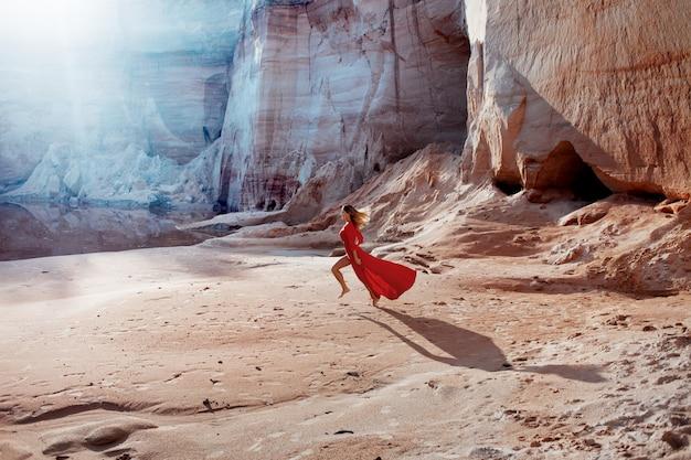 Frau im roten wellenartig bewegenden kleid mit fliegengewebe läuft auf der sandkarriere