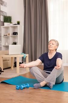 Frau im ruhestand, die sich im wohnzimmer auf yogamatte entspannt
