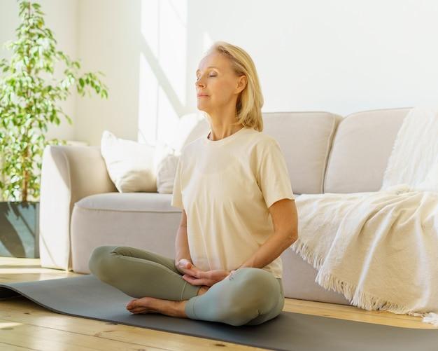 Frau im ruhestand meditiert und praktiziert yoga, während sie zu hause im lotussitz auf dem boden sitzt