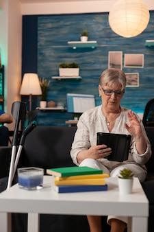 Frau im ruhestand winkt videoanrufkamera auf tablet