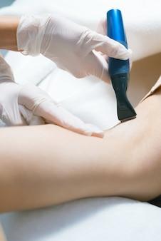 Frau im salon, die ein haarentfernungsverfahren auf achselhöhlen hat