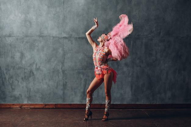 Frau im samba- oder lambada-kostüm mit rosa federkleid.