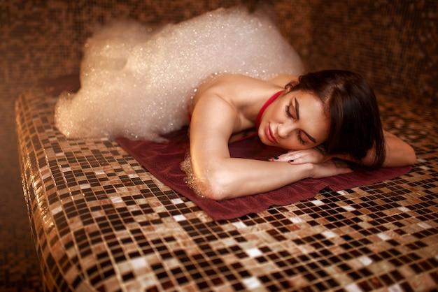 Frau im schaum, der auf einem heißen stein in hamam, sauna liegt