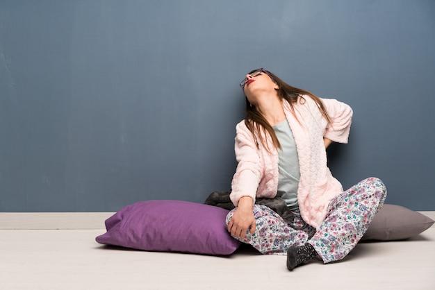 Frau im schlafanzug auf dem boden, die unter rückenschmerzen leidet, weil sie sich mühe gegeben hat