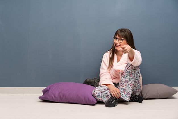 Frau im schlafanzug auf dem boden zeigt finger auf sie mit einem überzeugten ausdruck