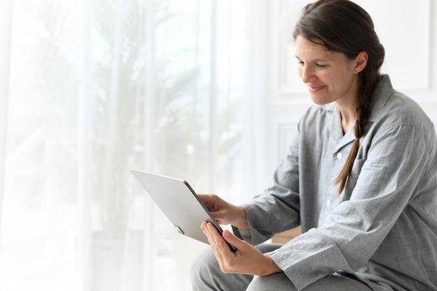 Frau im schlafanzug bei einem videoanruf auf einem tablet
