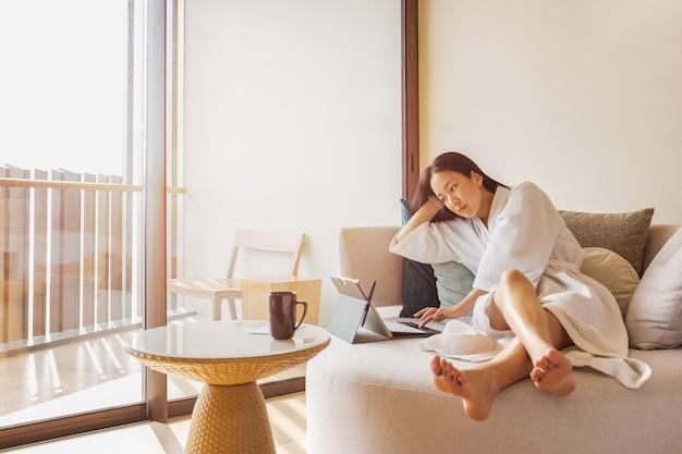 Frau im schlafrock sitzen auf der couch, die am laptop arbeitet