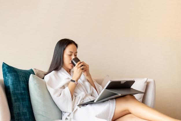 Frau im schlafrock sitzen in einer couch, die kaffee unter verwendung des laptops trinkt