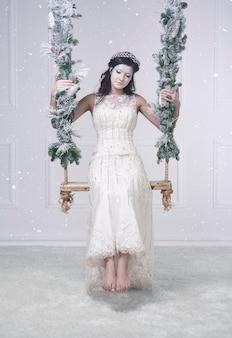 Frau im schneeköniginnenkostüm auf schaukel