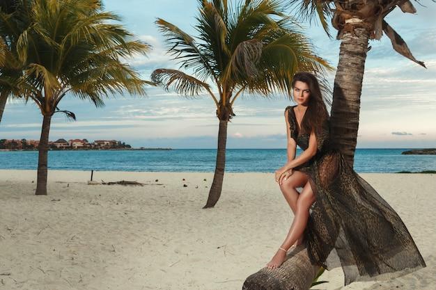 Frau im schönen kleid mit leopardenmuster am strand