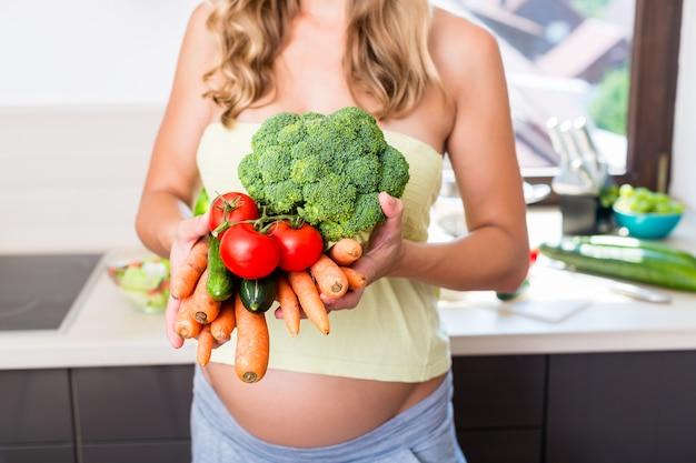 Frau im schwangeren essen des gesunden gemüses