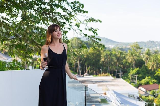 Frau im schwarzen abendkleid mit glas wein auf tropischem balkon