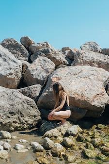 Frau im schwarzen badeanzug, der auf felsen nahe meer sich duckt