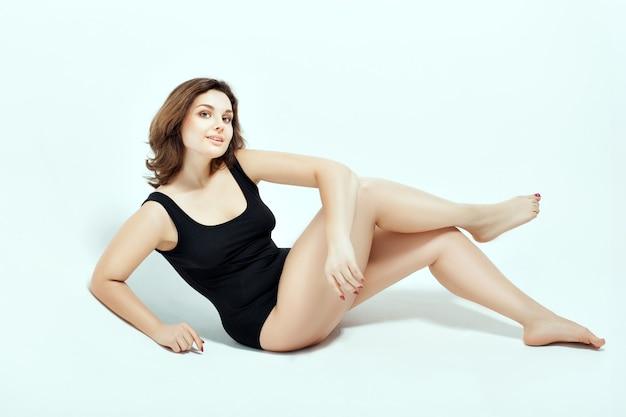 Frau im schwarzen badeanzug. sie sitzt auf seiner seite und verschränkt die beine