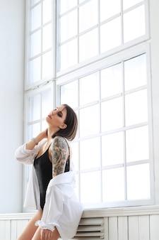 Frau im schwarzen badeanzug und im weißen hemd