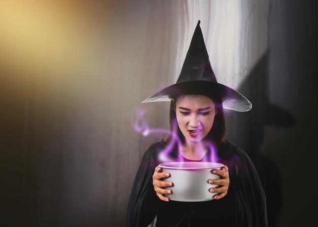 Frau im schwarzen beängstigenden hexenhalloween-kostüm, welches das kesselweite rauchgespenst der gespenstischen hexe hält