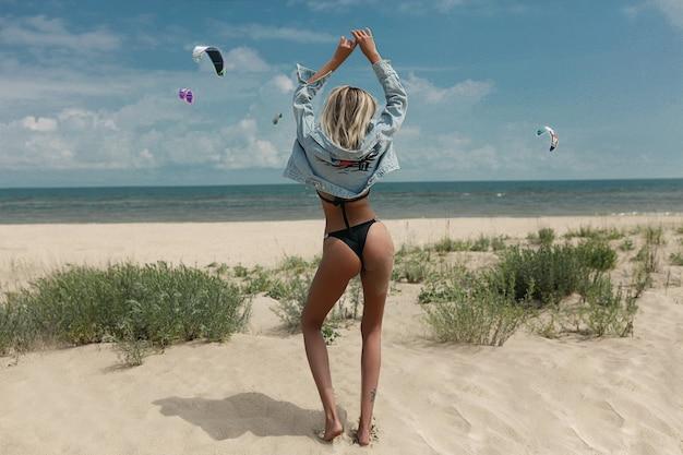 Frau im schwarzen bikini mit nassen haaren am strand bei sonnenuntergang
