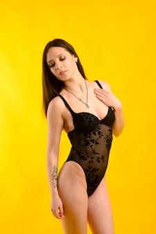 Frau im schwarzen body auf gelbem hintergrund. sinnlich wunderschöne frau posiert im studio