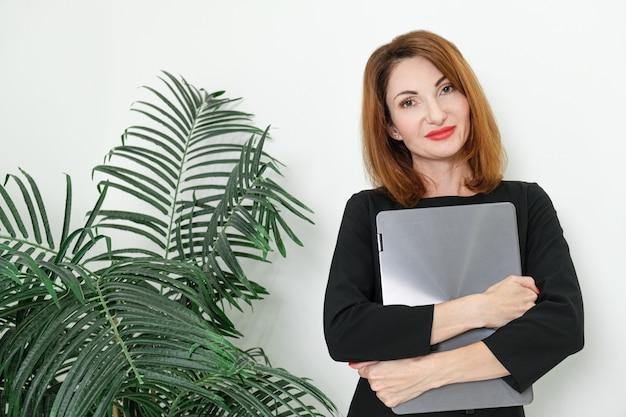 Frau im schwarzen business-kleid steht mit laptop in den händen frau wartet auf ein geschäftstreffen